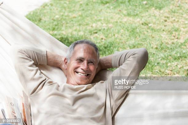 man in hammock, hands behind head looking at camera smiling - zurücklehnen stock-fotos und bilder