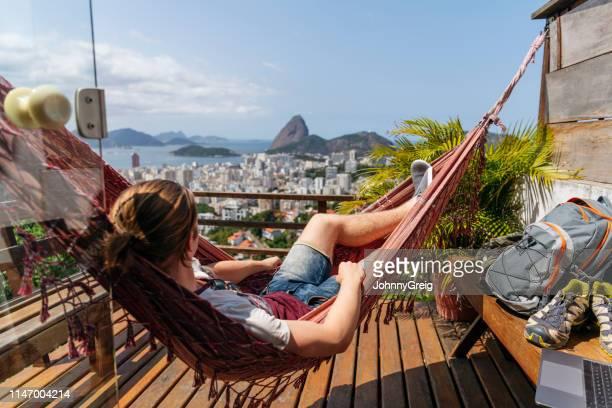 mann in hängematte auf balkon mit blick auf rio de janeiro - casa stock-fotos und bilder