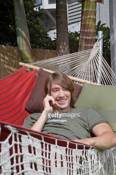 Man in hammock using cell phone