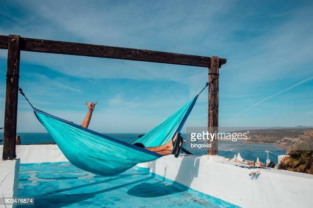 Man in hammock with hand raised showing a shaka sign