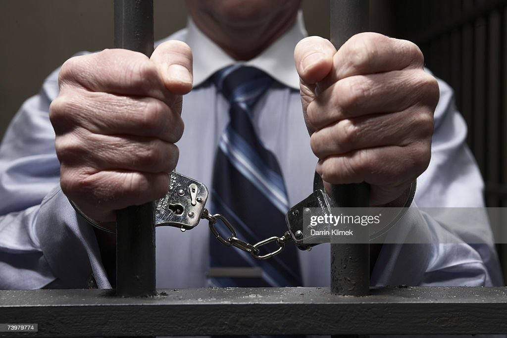 Man in handcuffs, holding prison bars, mid section, close-up of hands : Stock Photo