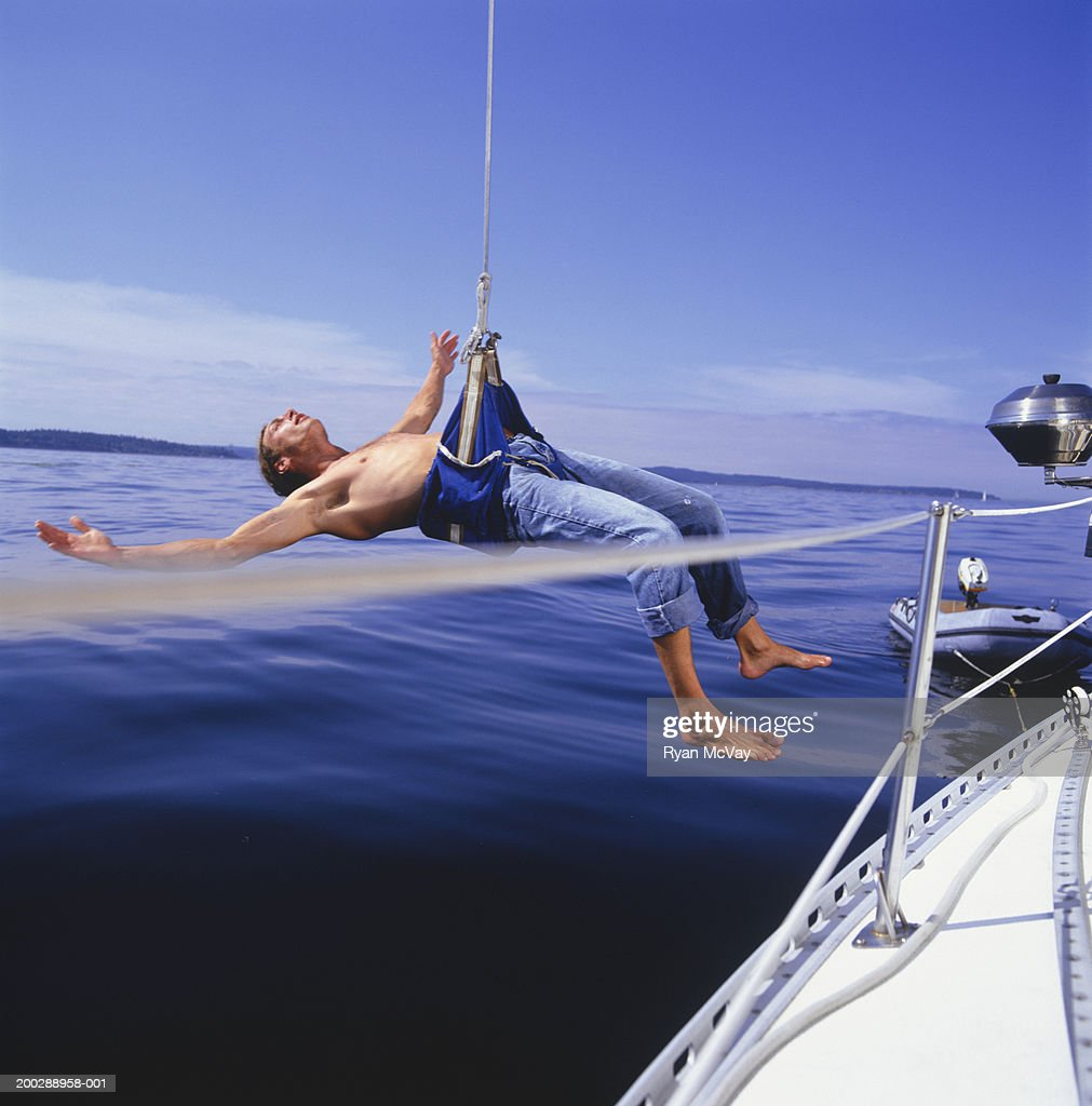 Man in harness from sailboat on ocean : Stock Photo