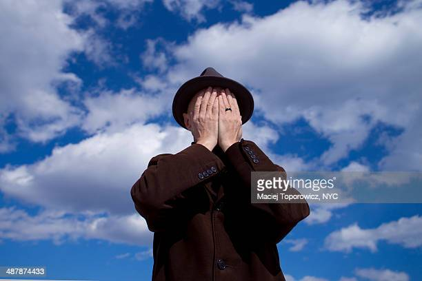 Man in hat covering his face against blue sky.