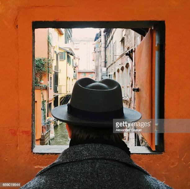 man in hat looking at the canal through the window in bologna, italy - culture foto e immagini stock