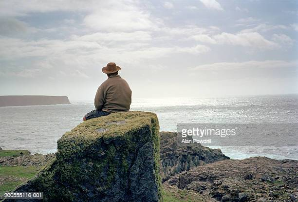Man in hat sitting on rock, looking at sea, rear view