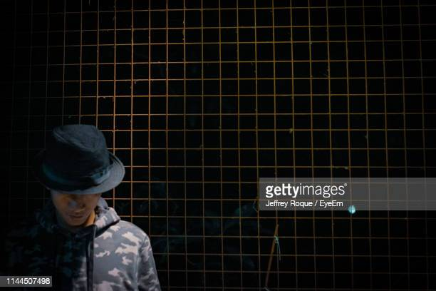 man in hat standing against fence - jeffrey roque stock photos and pictures