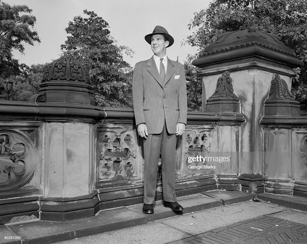 Man in hat standing by wall : Stock Photo