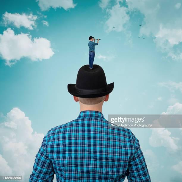 man in hat standing on a head of another person - personas cabeza grande fotografías e imágenes de stock