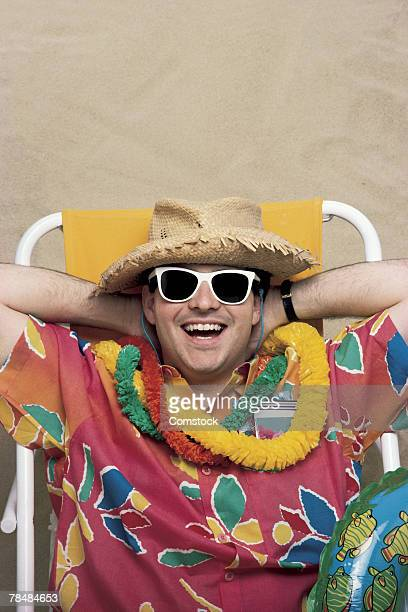Man in Hawaiian shirt on beach