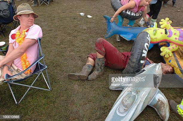 Man in Hawaiian shirt with flowers looks on as drunken revellers with inflatables fall over in front of the Pyramid Stage between bands at...