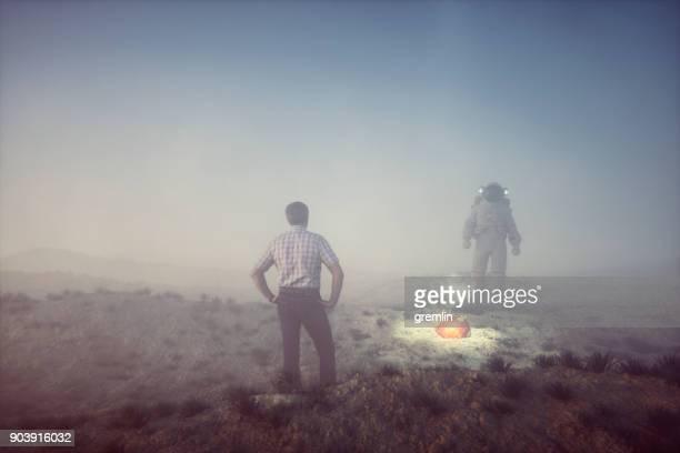 Man in hazmat suit picking up alien object