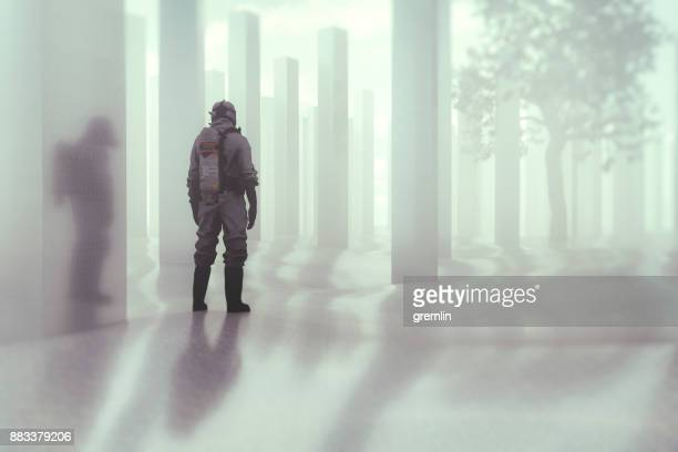 man in hazmat suit standing in futuristic field - hazmat stock pictures, royalty-free photos & images