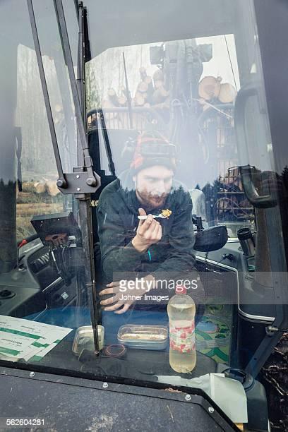 Man in heavy vehicle having lunch break