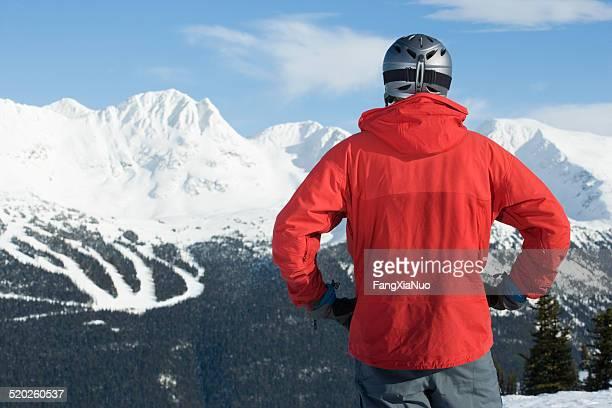 Mann mit Helm Stand vor schneebedeckten Bergen, Rückansicht