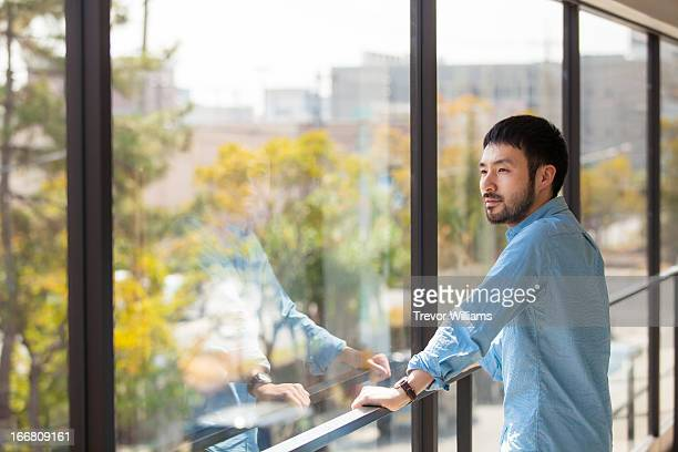 A man in his 30's standing at a window.
