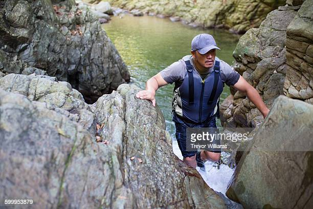 A man in his fifties climbs a small waterfall