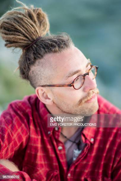 man in his twenties with long blonde dreadlocks - man bun stock pictures, royalty-free photos & images