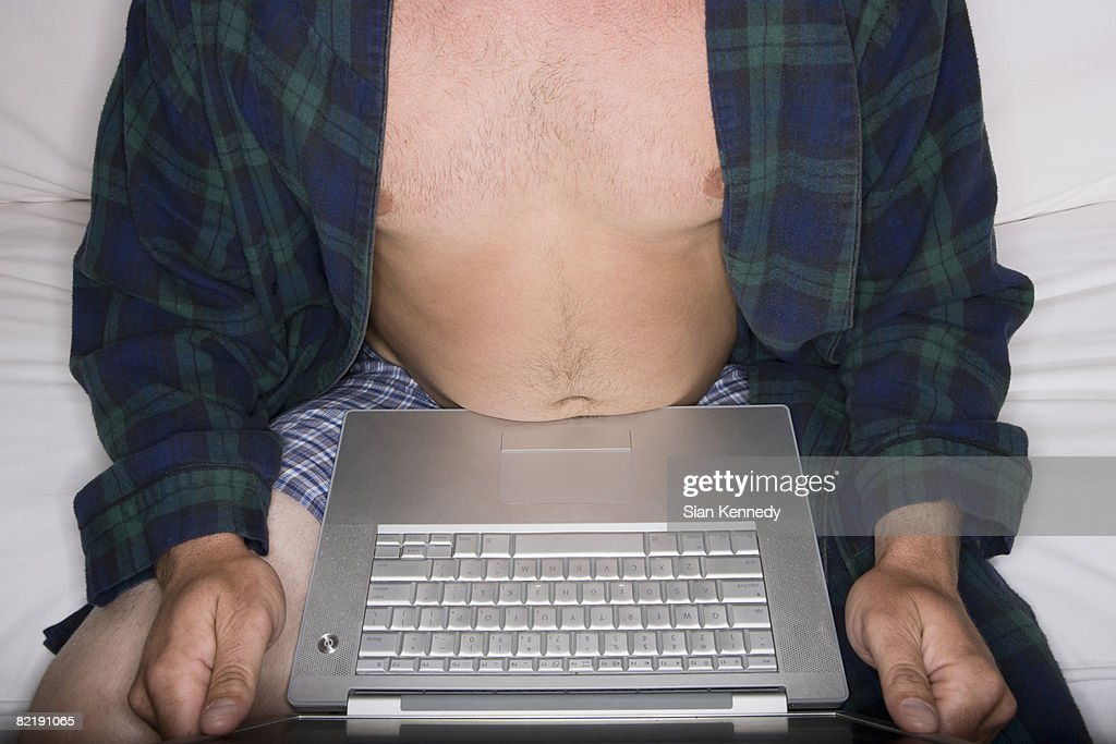 Man in his underwear using a laptop on the couch : Stock Photo