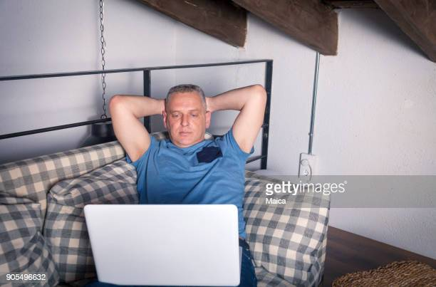 man in home watching movie on laptop - free download photo stock photos and pictures