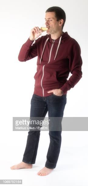 man in hood clothing drinking wine against white background - パーカー服 ストックフォトと画像