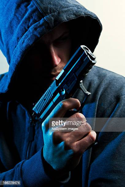 man in hood with revolver - armed robbery stock photos and pictures