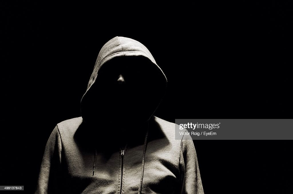 Man in hooded jacket over black background : Stock Photo