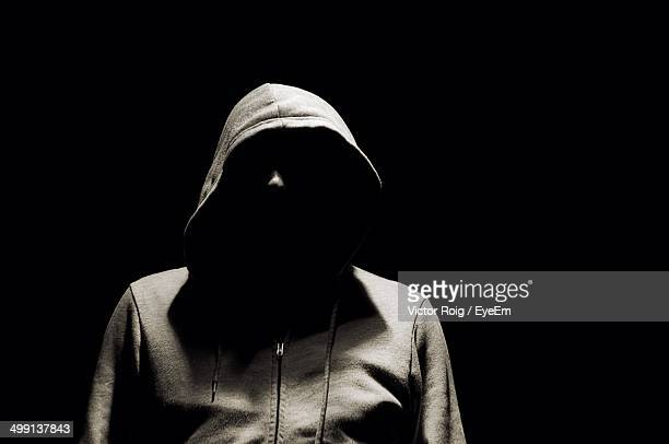Man in hooded jacket over black background