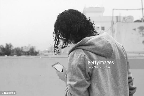 Man In Hooded Shirt Using Phone
