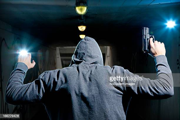 man in hoodie with gun surrendering with arms up - armed robbery stock photos and pictures
