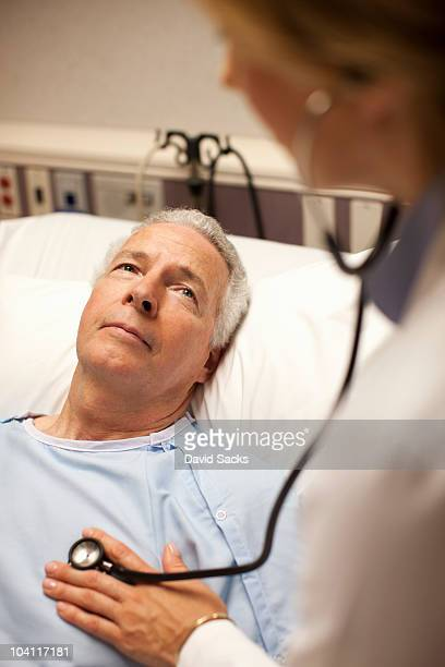 Man in hospital bed looking up at female doctor