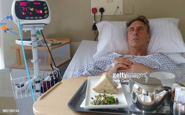 Man in hospital bed with food on tray