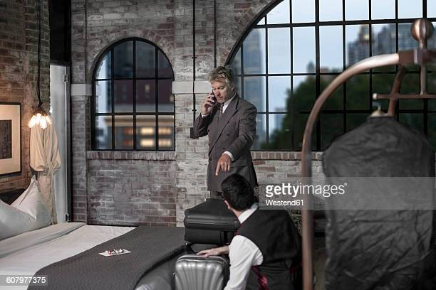 Man in hotel room talking on phone, bell boy bringing suitcase