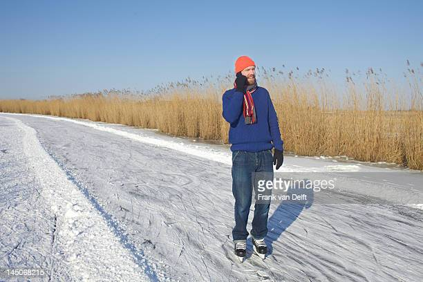 Man in ice skates talking on cell phone