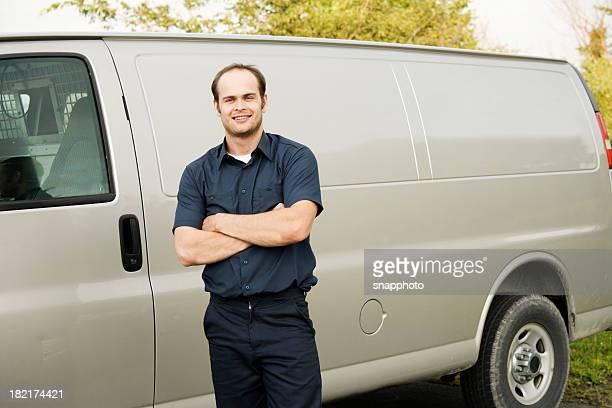 Man in Industrial Uniform Standing Next to Service Van