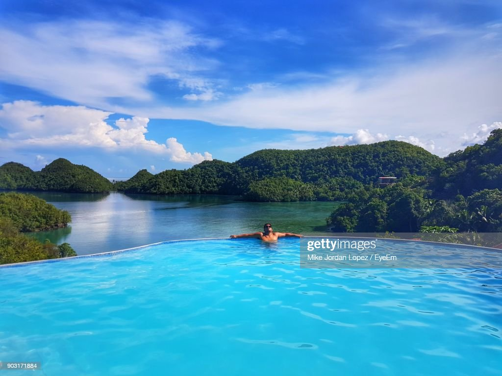 Man In Infinity Pool Against Sky : Stock Photo