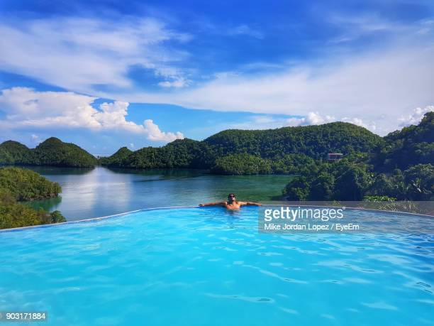 man in infinity pool against sky - metro manila stock photos and pictures