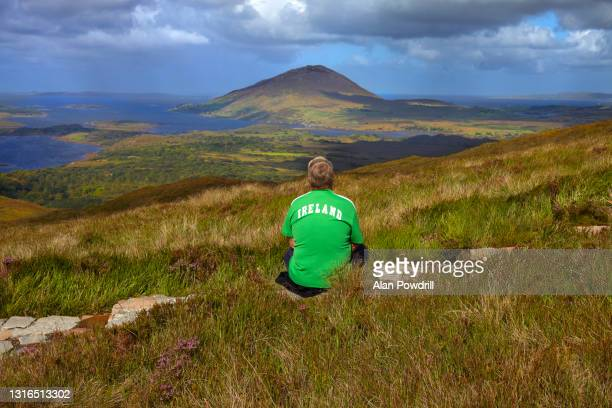 man in ireland t-shirt sitting in irish landscape - graphic print stock pictures, royalty-free photos & images