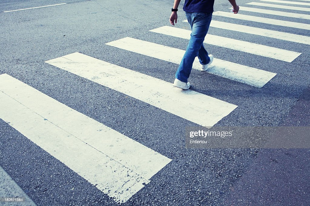 Man in jeans walking across a zebra crossing : Stock Photo