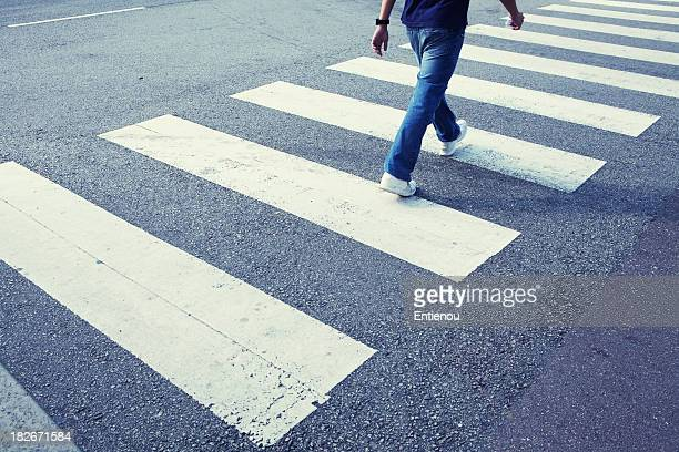 man in jeans walking across a zebra crossing - pedestrian crossing stock photos and pictures