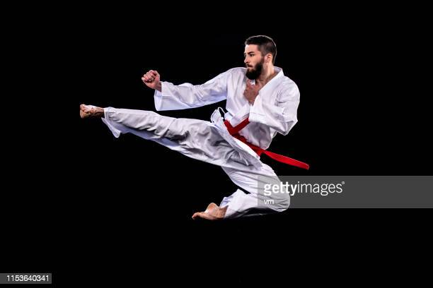 man in kimono performing a flying kick against a black background - martial arts stock pictures, royalty-free photos & images