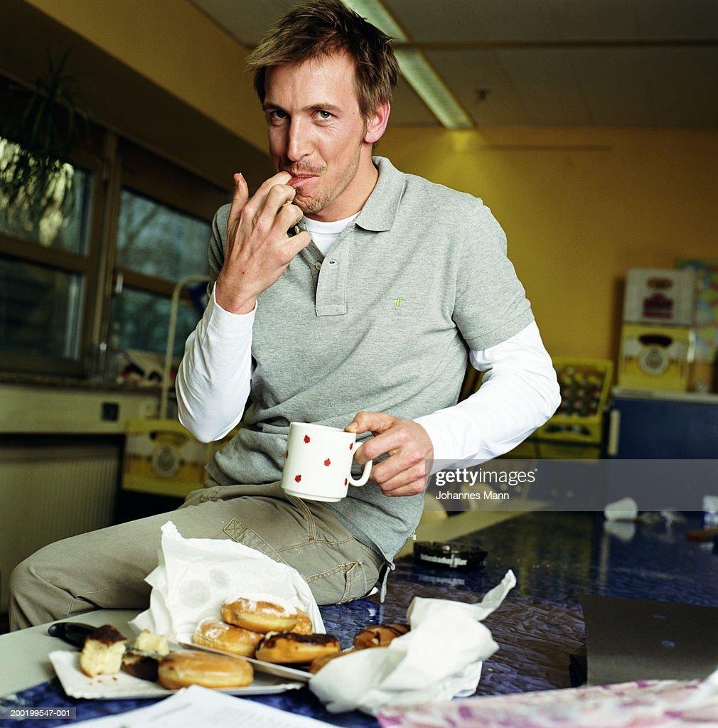 Man in kitchen by doughnuts, licking fingers, portrait : Stock Photo