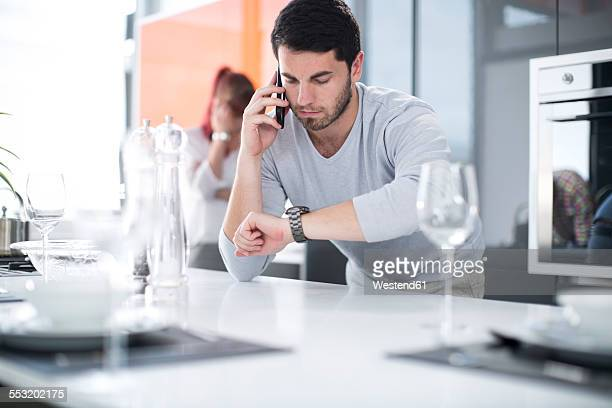man in kitchen checking the time and talking on cell phone - watch timepiece stock pictures, royalty-free photos & images