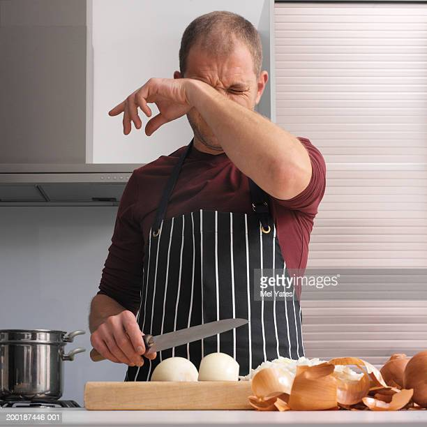 Man in kitchen chopping onions, wiping eye with back of hand