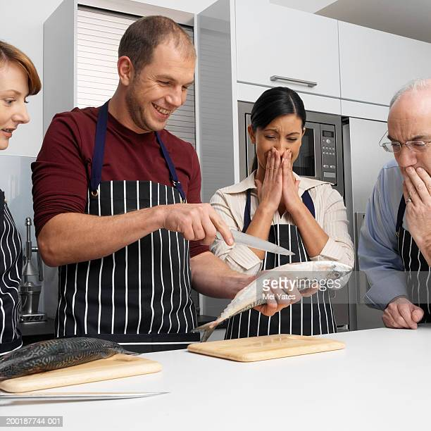 Man in kitchen demonstrating fish gutting