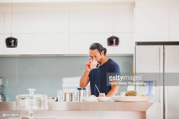 Man in kitchen having cup of tea.