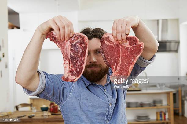 Man in kitchen holding two steaks