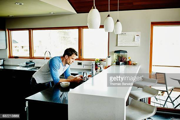 Man in kitchen of home checking smartphone