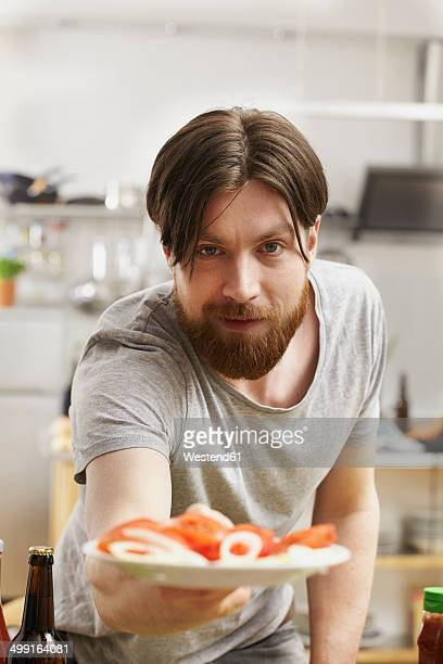 Man in kitchen offering plate with tomatoes