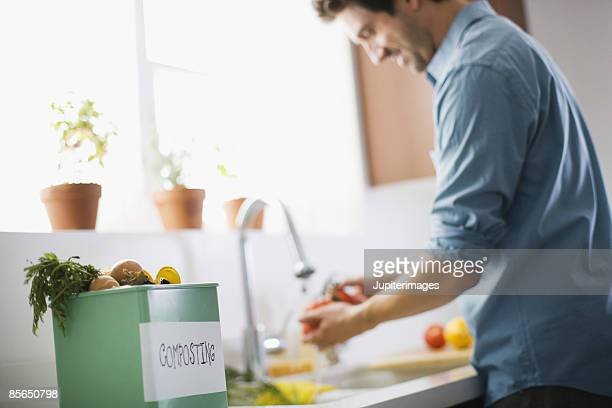 Man in kitchen with compost bin