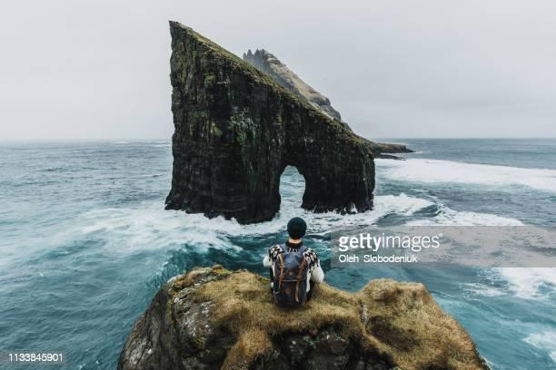 hombre en suéter de punto mirando a la vista del arco drangarnir en las islas feroe - islas faroe fotografías e imágenes de stock